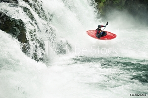 Picture of Whitewater kayaker paddling through river in forest